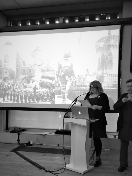 Black and White image of artist Lauren Saunders standing at a podium. The large screen behind her shows two surreal collages she created.